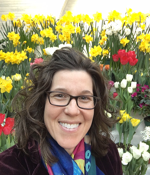 Abby standing in front of daffodils and tulips
