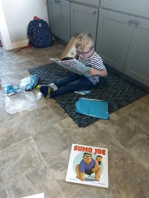 boy reading picture book called Eraser